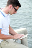 College student browsing internet using his tablet Stock Photo