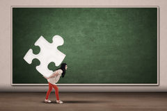 College student carrying piece of puzzle. Female college student carrying a piece of puzzle on her back Stock Photo