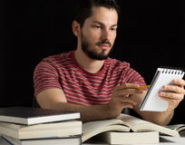 College student checking notes. Young male reviewing personal notes during studies Stock Image