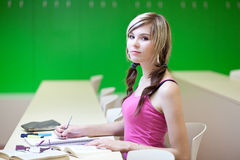 College student in a classroom. Portrait of a pretty young college student in a classroom Royalty Free Stock Images