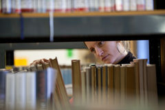 College student in a college library. Pretty female college student in a college library (shallow DOF; color tuned image Stock Photo