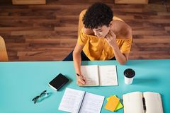 College student copying notes. High angle view of african girl studying in library. Young brazilian student copying notes from book at cafeteria. Top view of royalty free stock image