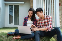 College student couple in the park with laptop royalty free stock images