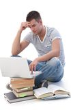 College student doing homework on laptop. College student using laptop, sitting on floor, doing homework Stock Photos