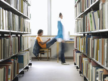 College Student Doing Homework In Library. Side view of a young male college student doing homework in the library stock images
