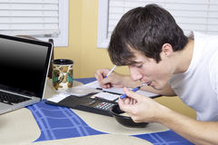 College Student eating breakfast. College student eats breakfast at the kitchen table after a late night of studying royalty free stock image
