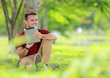 College student enjoy sitting under the tree while playing a tab Stock Photos