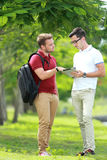 A college student explaining a subject to his friend Stock Photography