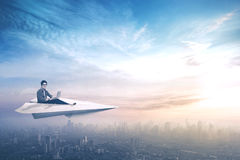 College student flying on paper aircraft Stock Photo