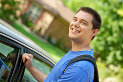 College student getting in car. A college student with backpack getting into his car to go off to school Royalty Free Stock Photos