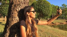 College Student Girl Making Selfie Photo Shots on Smartphone Sitting in the Park. Slowmotion HD. stock footage