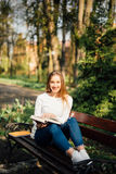 College student girl reading a book sitting on bench in city park Royalty Free Stock Photography