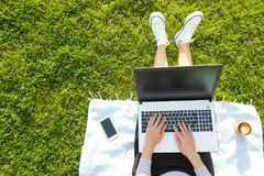 College student girl sitting on the green lawn doing homework on her laptop computer. Young woman sitting at the park blogging, wr. Young fit attractive woman Royalty Free Stock Image
