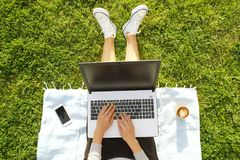 College student girl sitting on the green lawn doing homework on her laptop computer. Young woman sitting at the park blogging, wr. Young fit attractive woman Stock Photos