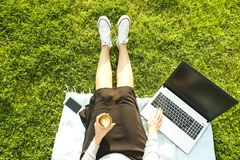 College student girl sitting on the green lawn doing homework on her laptop computer. Young woman sitting at the park blogging, wr. Young fit attractive woman Stock Images