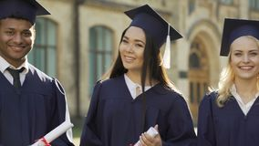 College student in graduation outfit with diplomas smiling, education abroad
