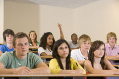 College student with hand raised in lecture Royalty Free Stock Photo