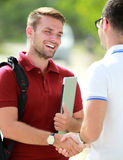 A college student happy to meet his friend and then shake hands stock images
