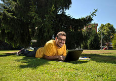College student with her computer. College student lying on the grass in the sun with a computer Stock Photography