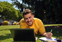 College student with her computer. College student lying on the grass in the sun with a computer Royalty Free Stock Photo