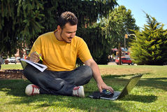 College student with her computer. College student lying on the grass in the sun with a computer Stock Photos