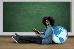 College student holding book with globe. Afro college student holding a book while sitting with a globe and smiling at the camera Stock Photo