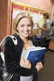 College Student Holding Books. Portrait of a young women holding books with friend in the background Royalty Free Stock Photo