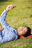 College Student Holding Mobilephone While Lying On. Side view portrait of young college student holding mobilephone while lying on grass at campus Royalty Free Stock Photo
