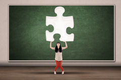 College student holding piece of puzzle Royalty Free Stock Photo