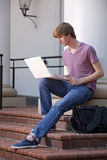 College Student with Laptop. Vertical photograph of a young male college student using a laptop Stock Image