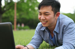 College student with laptop. Laying on the grass smiling Stock Photos