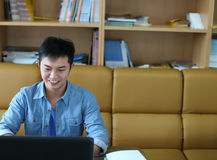 College student with laptop. Indoor and smiling Stock Photography