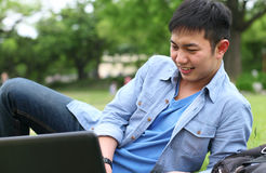 College student with laptop. Laying on the grass smilling Stock Photos