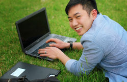 College student with laptop. Laying on the grass smilling Royalty Free Stock Photos