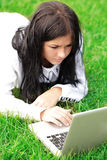 College student with laptop on the grass Royalty Free Stock Photo