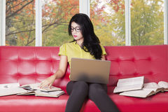 College student with laptop reads books on sofa. Female college student using notebook computer while reading books and studying on the red sofa at home Stock Images