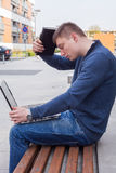 College student learning over the bench with laptop. Portrait of. A shocked male student looking at the monitor of his laptop. So much work ahead Royalty Free Stock Photo