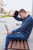 College student learning over the bench with laptop. Portrait of. A shocked male student looking at the monitor of his laptop. So much work ahead Stock Photography