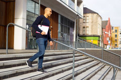 College student. Student leaving college holding his textbooks and rucksack Royalty Free Stock Images