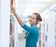College student in a library. Pretty young college student in a library (shallow DOF; color toned image Stock Image