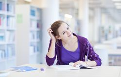 College student in a library. Pretty young college student in a library (shallow DOF; color toned image Stock Photo
