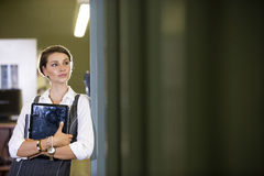 College student at library doorway holding laptop. Pretty female university student at library doorway holding laptop in arms Stock Images