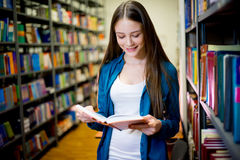 College student in library. College student reading book in university library Royalty Free Stock Images