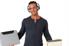 College student listening to music. A happy handsome male college student listening to music on headphones Stock Image