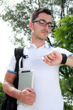 College student looking at the time on his watch. While holding tablet Royalty Free Stock Image