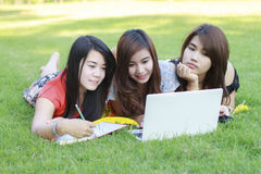 College student lying down on the grass working Stock Photo