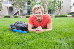 College student lying in the grass. Portrait of a college student lying in the grass Royalty Free Stock Image