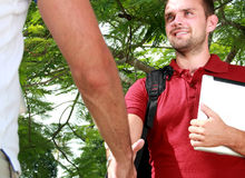 College student meet his friend and then shake hands Stock Photos