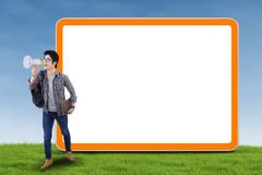College student with megaphone. Male college student with megaphone and blank board with copy space outdoor Royalty Free Stock Photos