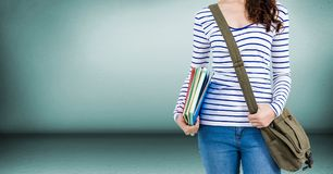 College student mid section with bag and books against green wall Stock Photography
